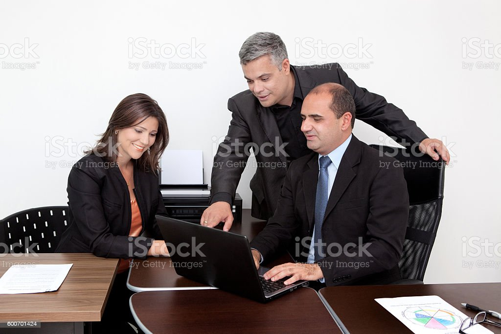Latin Business Coach Giving Instructions Pointing at Laptop at Office stock photo