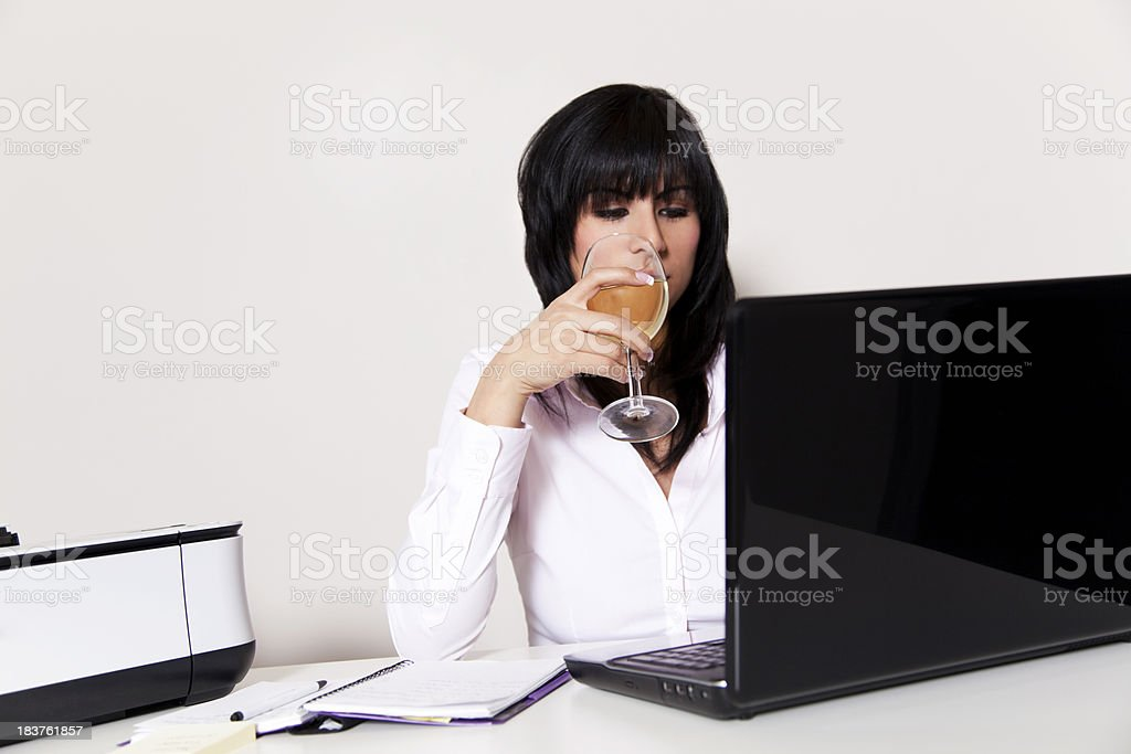 Latin businesswoman on laptop with a glass of wine royalty-free stock photo