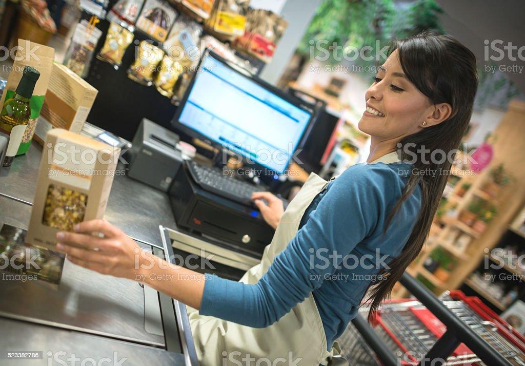 Latin cashier working at a supermarket stock photo