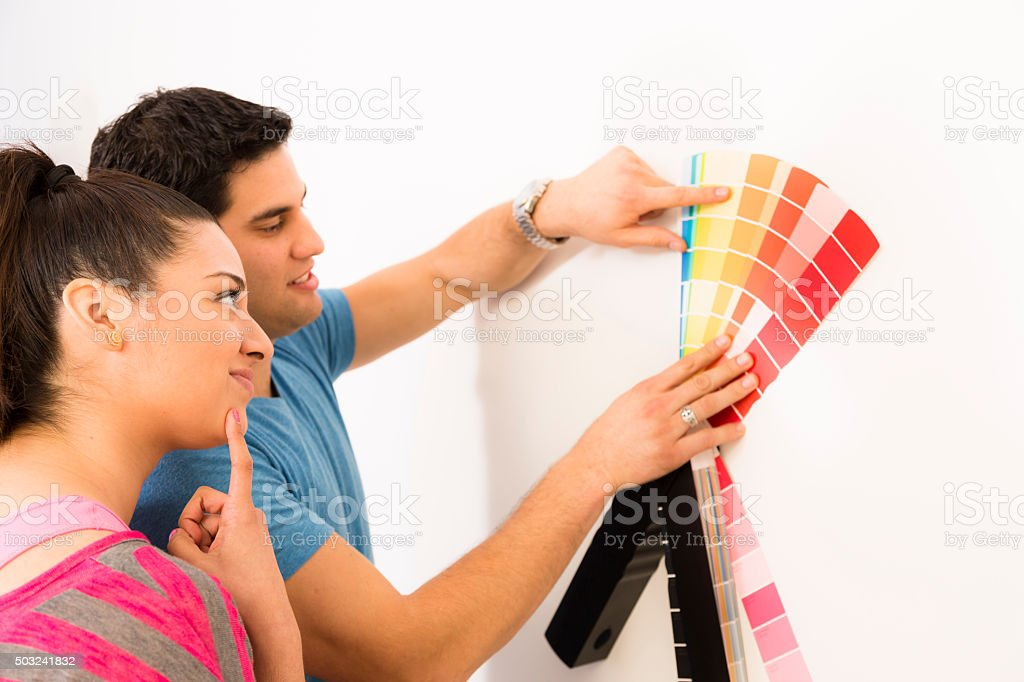 Latin couple choose paint color for wall in home. stock photo