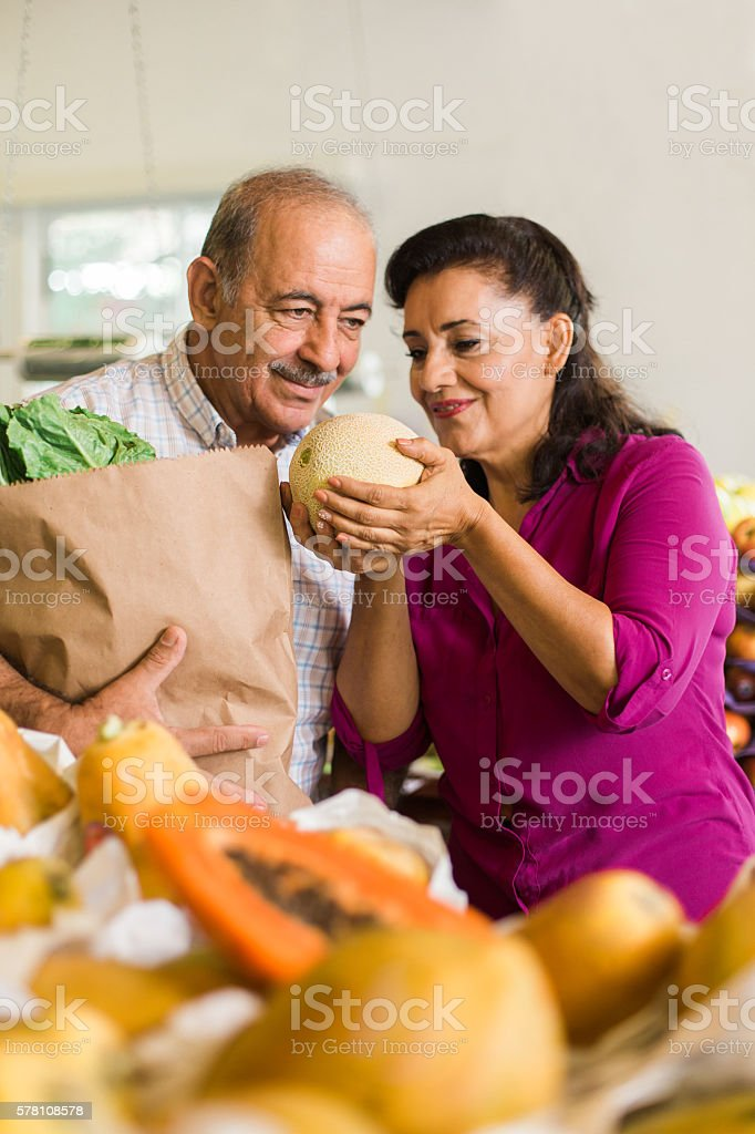 Latin couple holding and smelling melon at supermarket stock photo