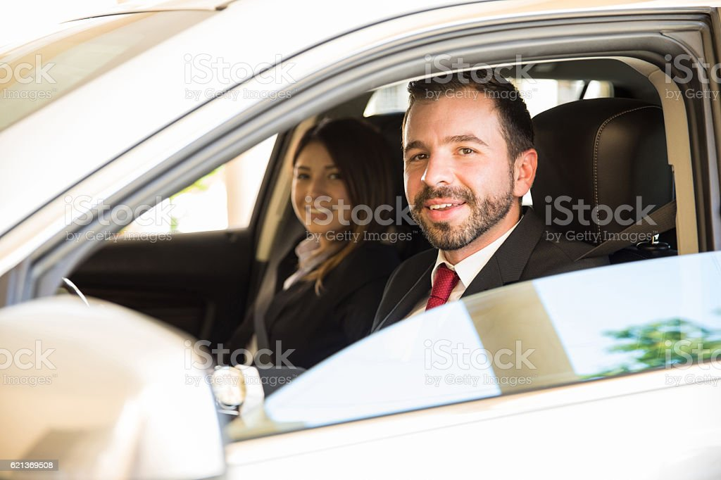 Latin coworkers driving on a business trip stock photo