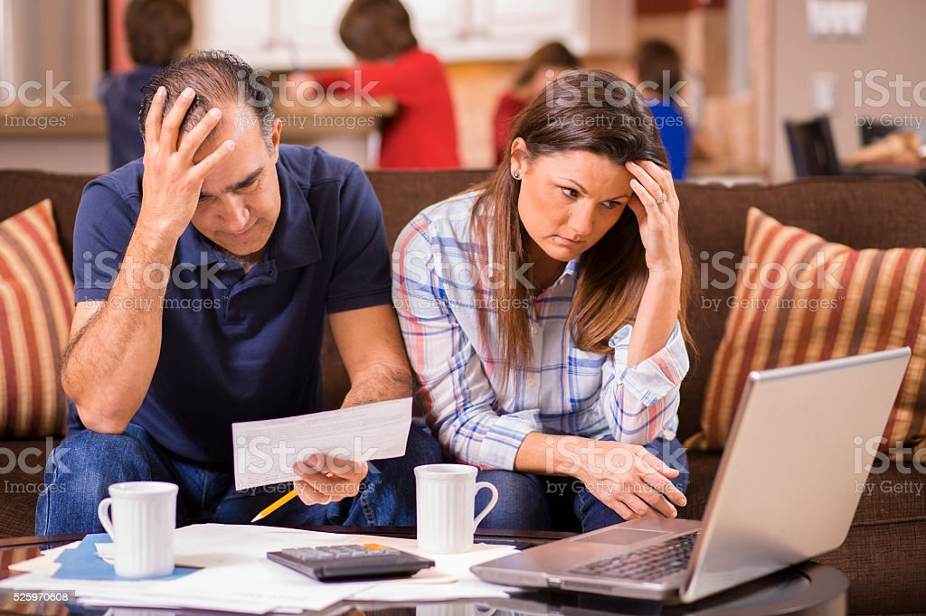 Latin descent couple paying monthly bills at home.  Frustration. stock photo