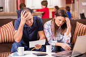Latin descent couple paying monthly bills at home.  Frustration.
