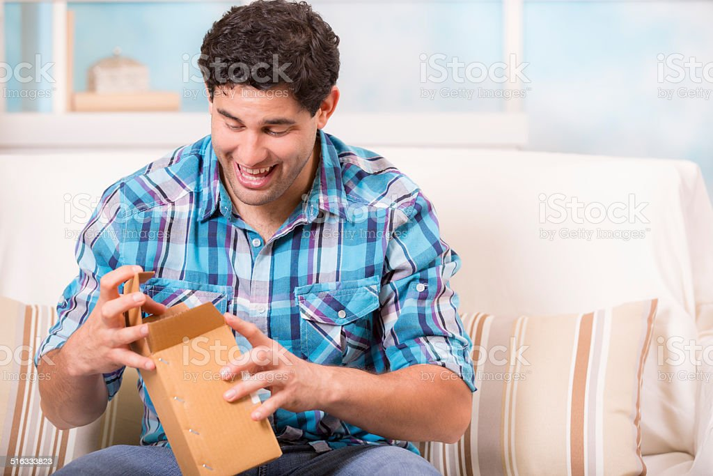Latin descent man opens a postal package he received. Home. stock photo