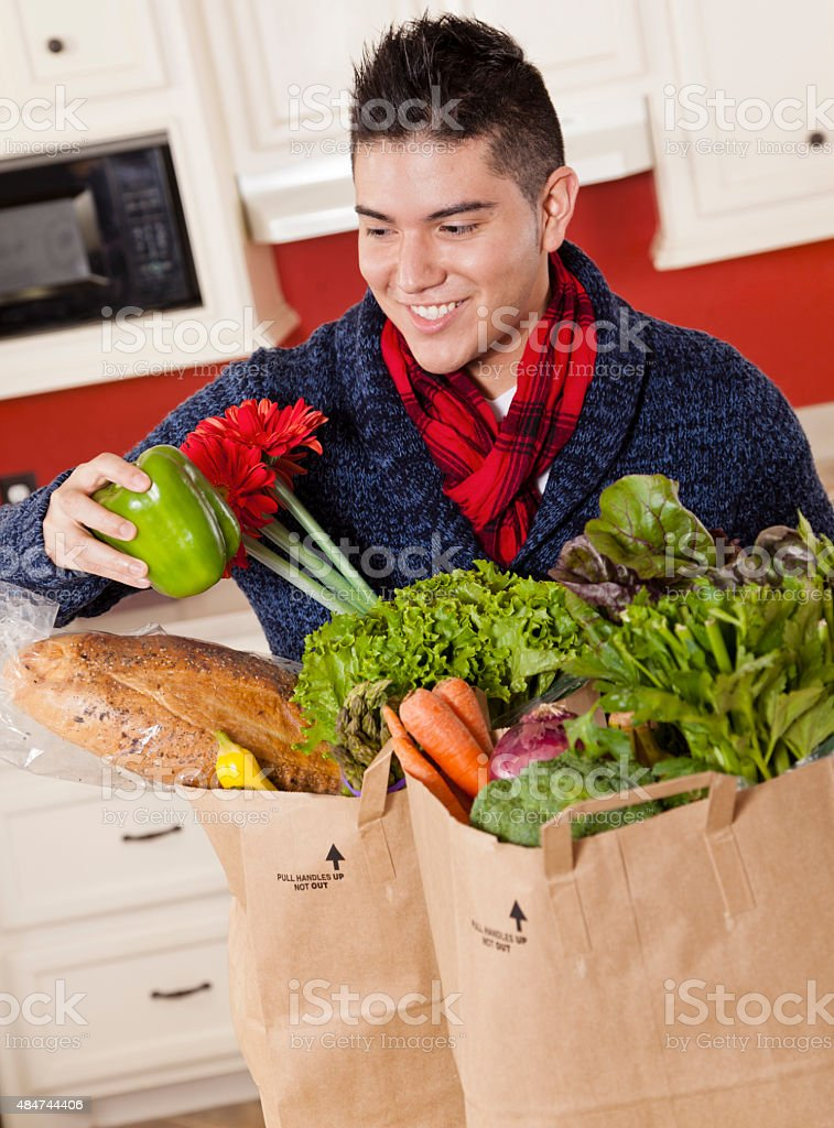 Latin descent man with grocery sacks in home kitchen. stock photo
