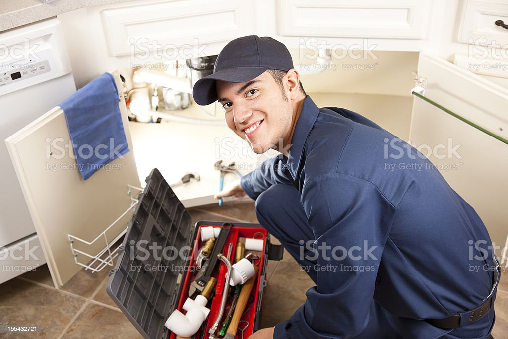 Latin descent plumber, repairman working under sink in home kitchen. stock photo