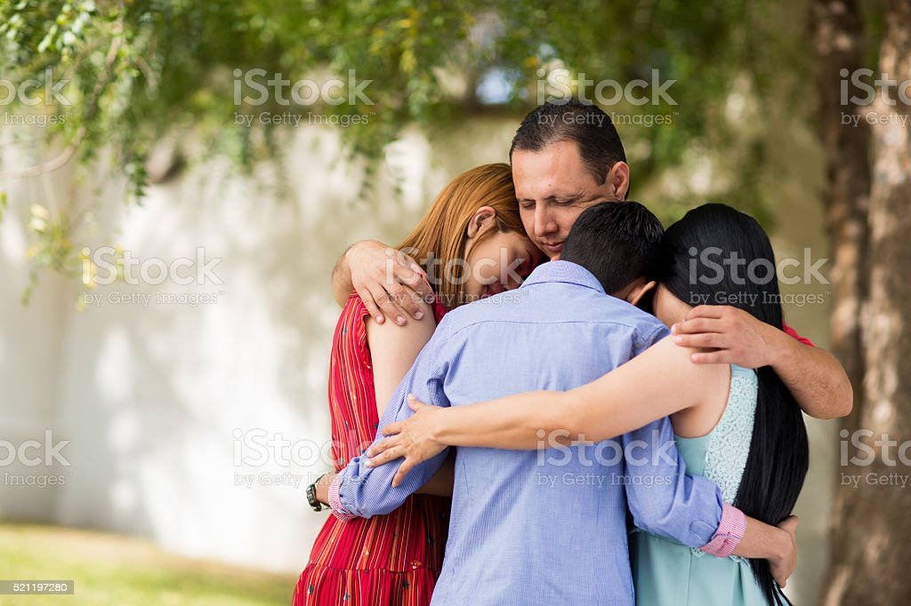 Latin family praying and embracing outdoors stock photo