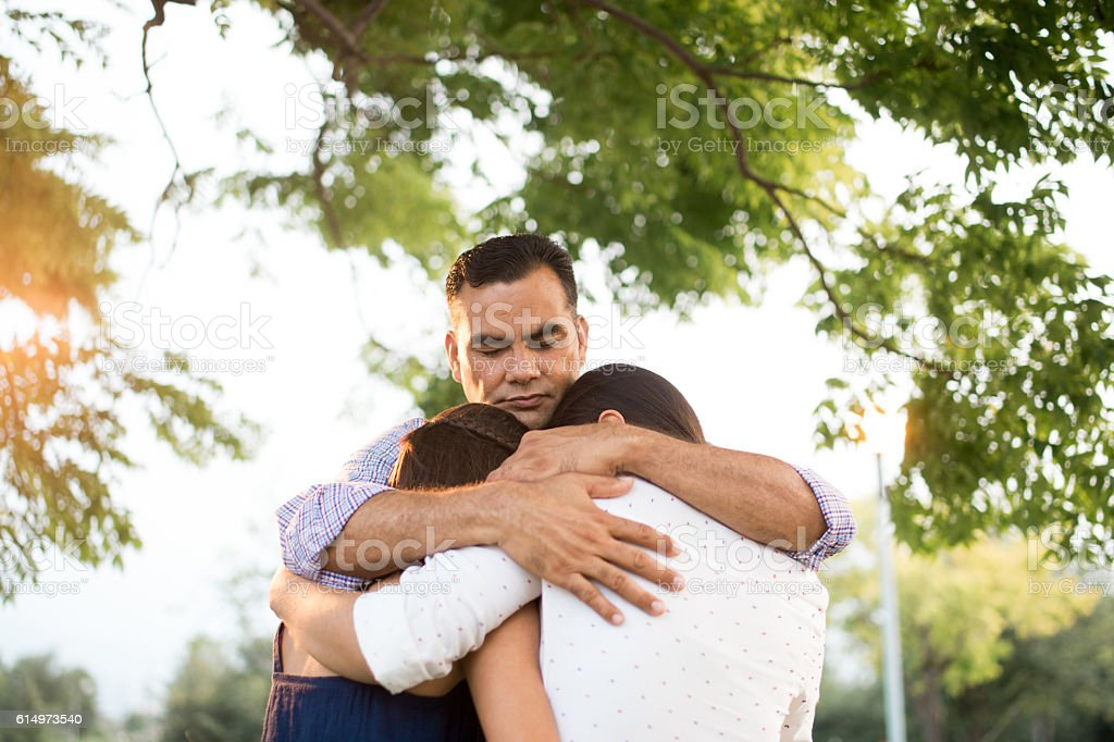Latin father and daughters embracing in circle stock photo