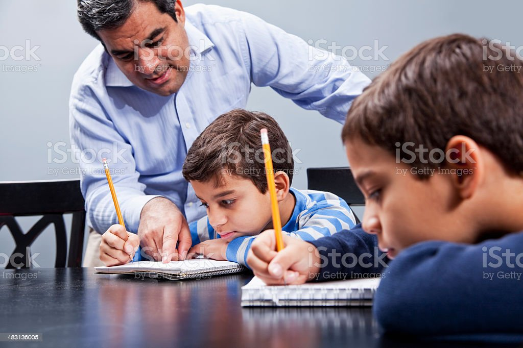 Latin father helping boys with homework royalty-free stock photo