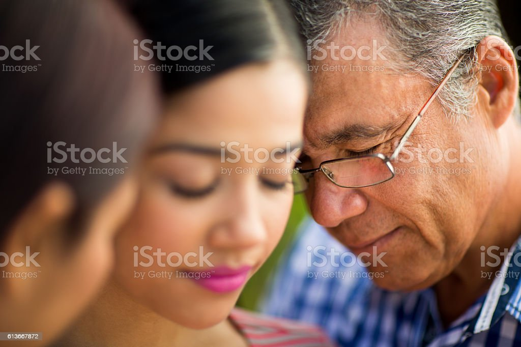 Latin father praying with wife and daughter stock photo