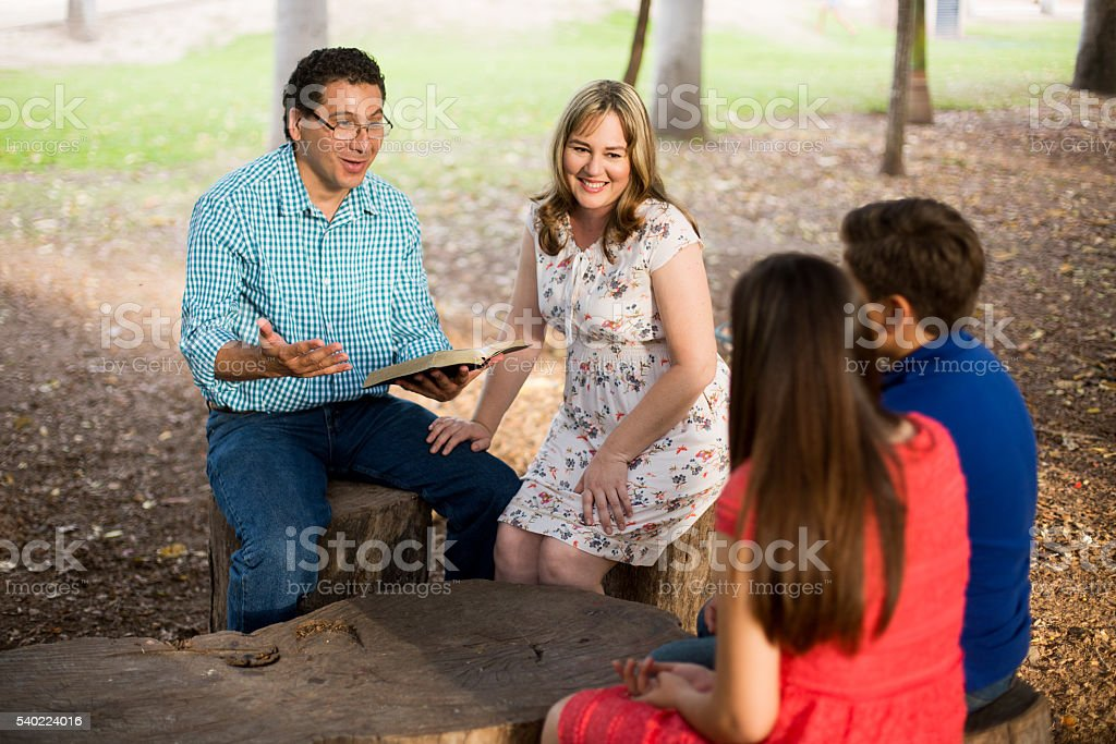 Latin father reading the Bible to teenage children outdoors stock photo