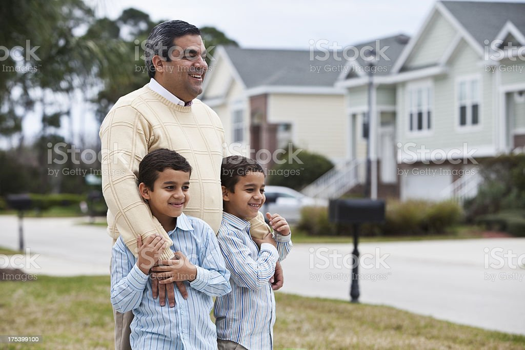 Latin father standing with twin boys in front yard royalty-free stock photo