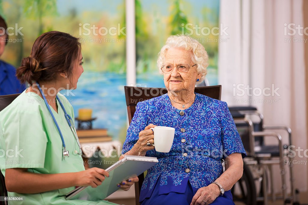 Latin, female doctor visits elderly woman patient in nursing home. stock photo