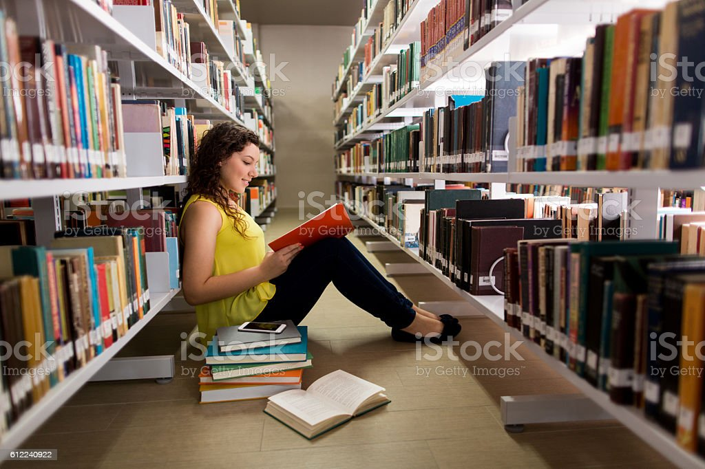 Latin female student reading a book on the floor stock photo