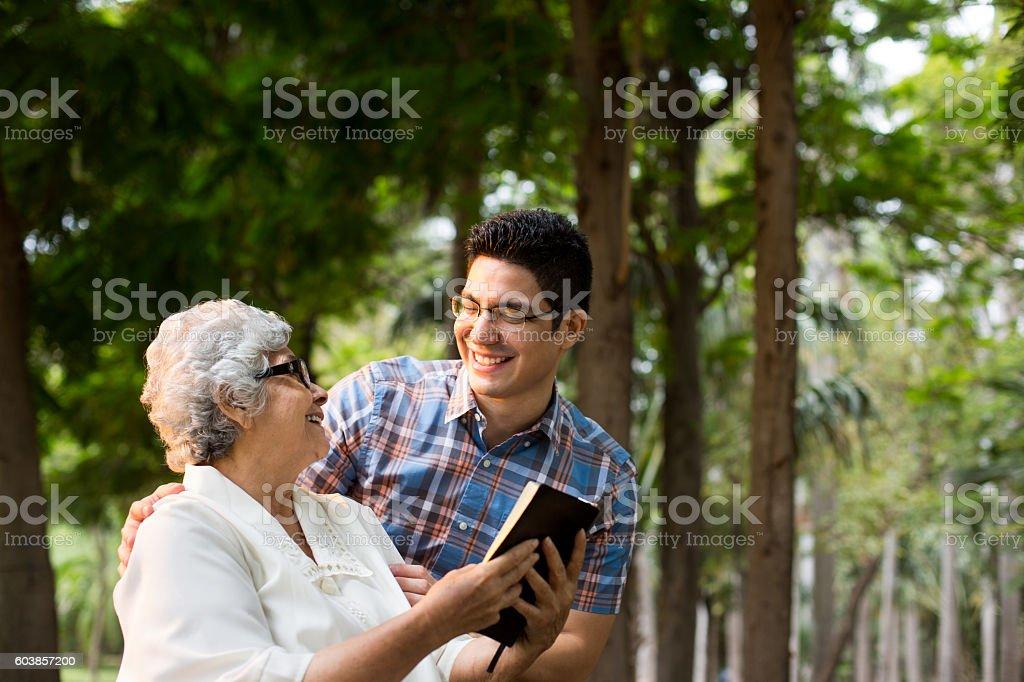 Latin grandmother reading Bible and smiling at grandson stock photo