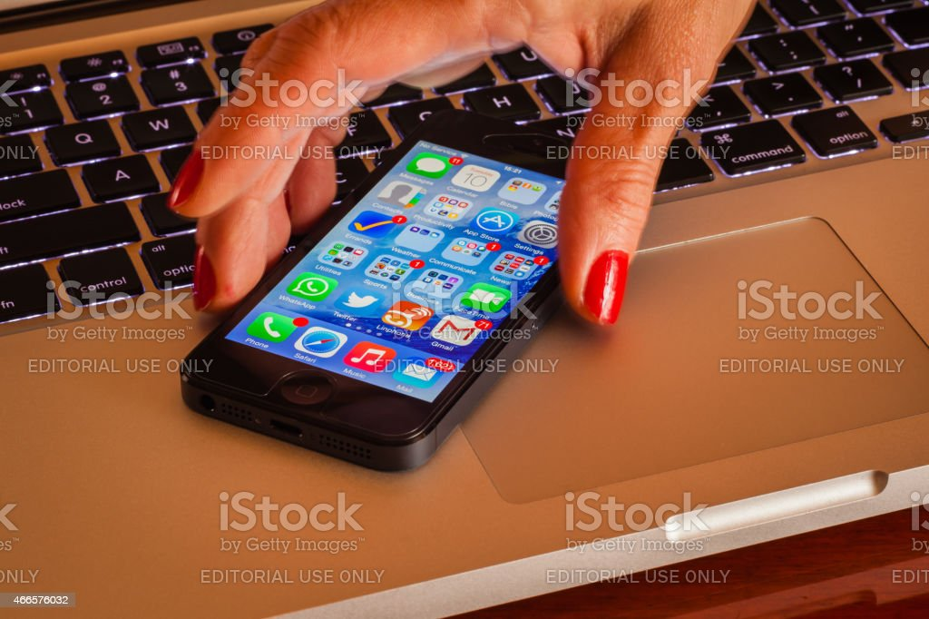 Latin lady's fingers picking up iPhone5 from computer keyboard; close-up stock photo