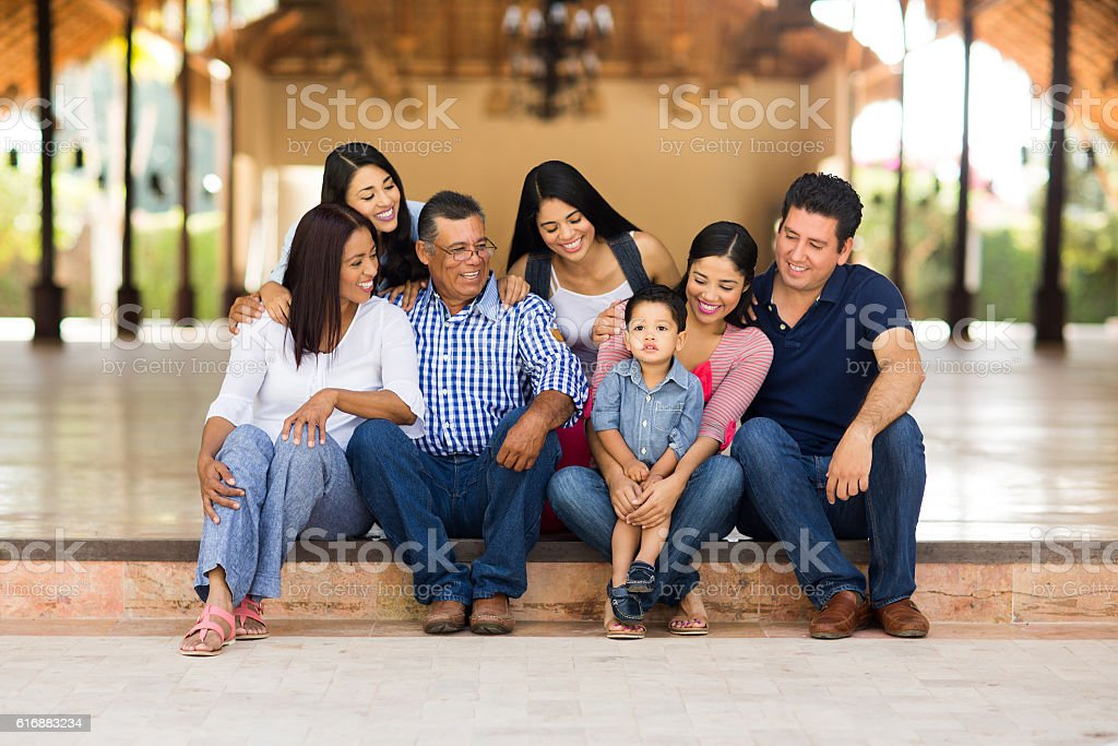 Latin large family sitting and looking at the little boy stock photo