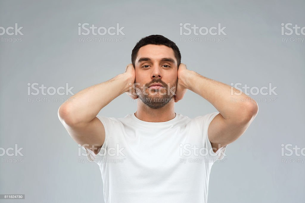 latin man covering his ears with hand palms stock photo