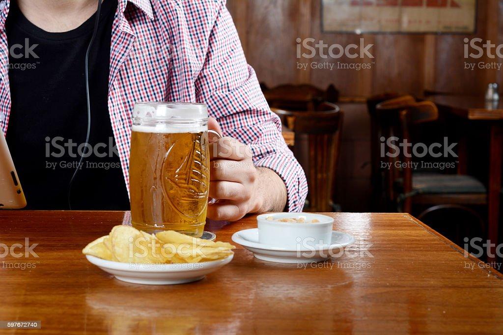 Latin man drinking beer and eating snacks at a bar stock photo