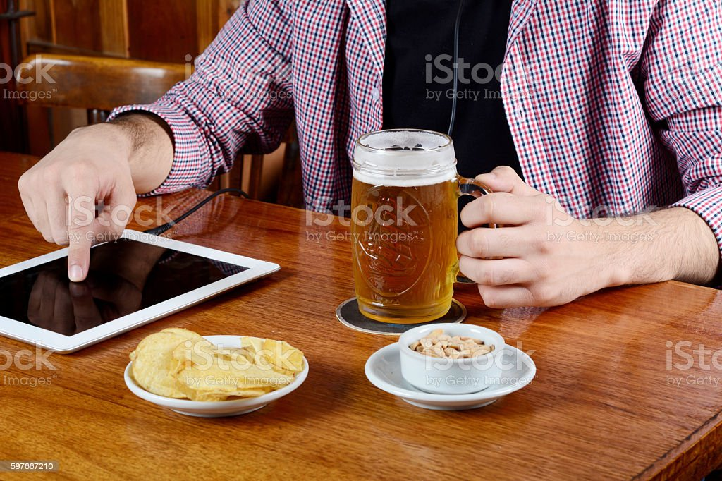 Latin man drinking beer with tablet and snacks. stock photo