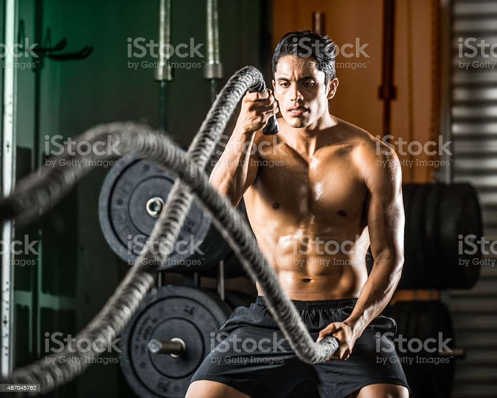 Latin Man Excerising With Ropes stock photo