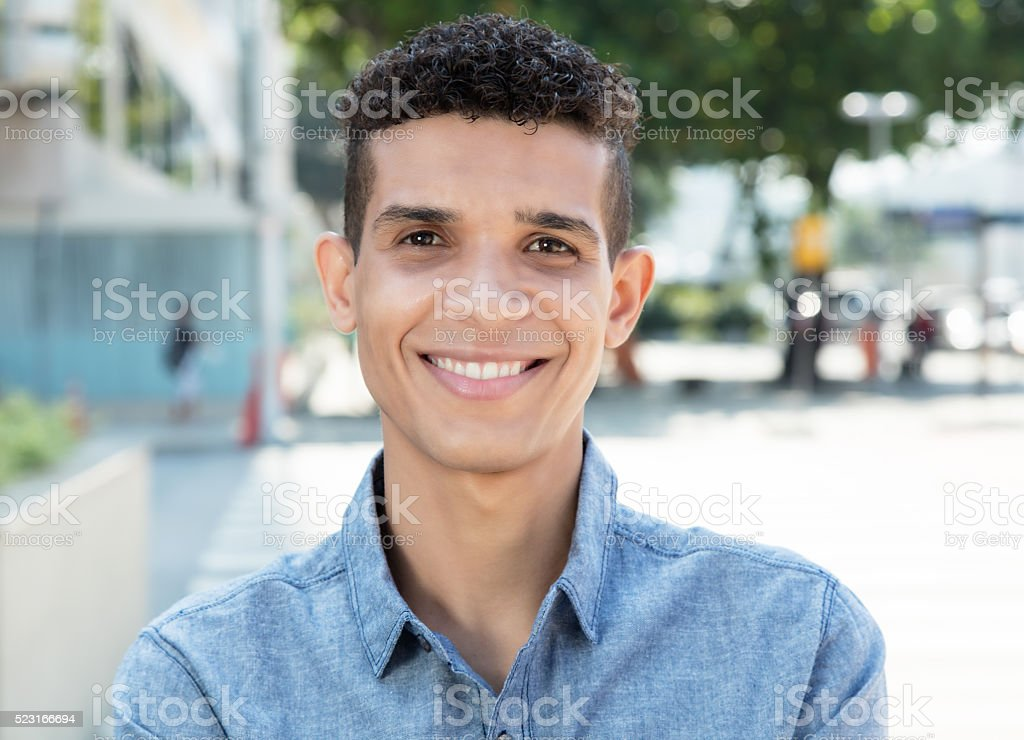 Latin man looking at camera in the city stock photo