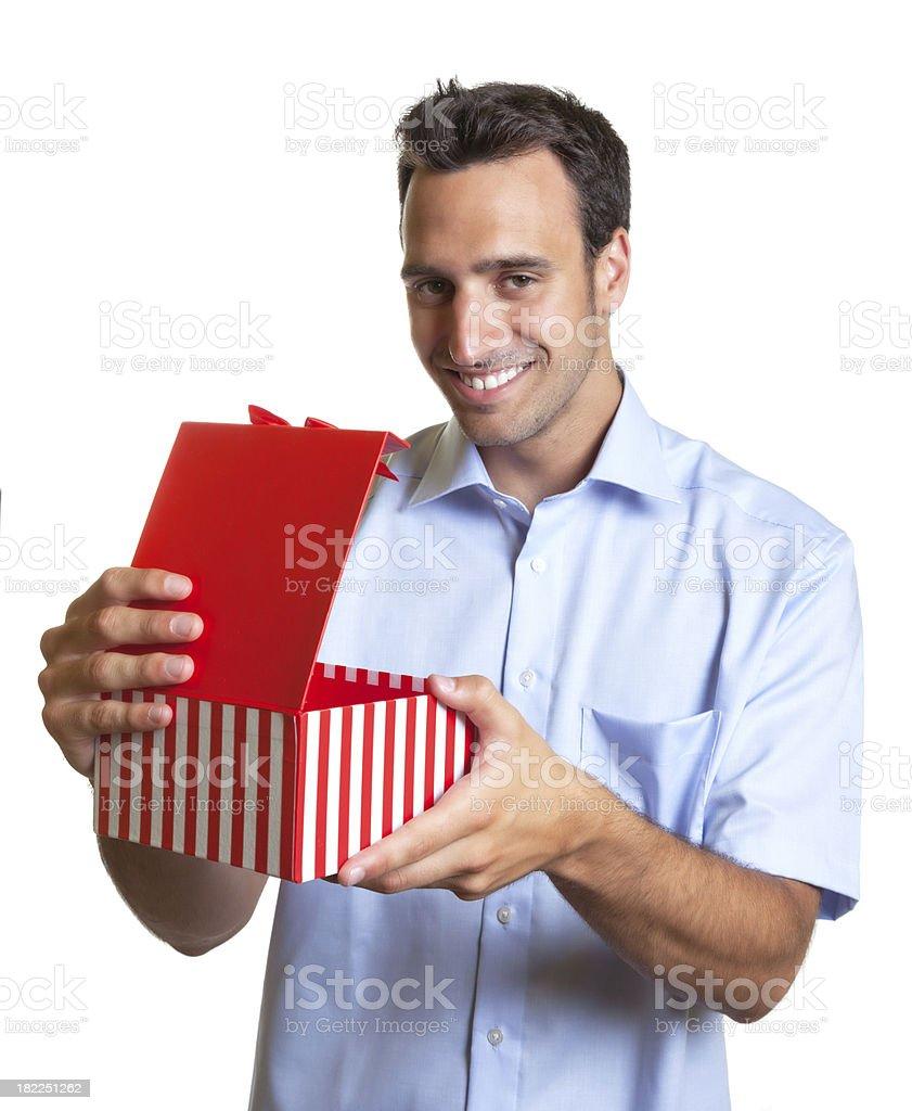 Latin man looking at camera with a christmas gift royalty-free stock photo