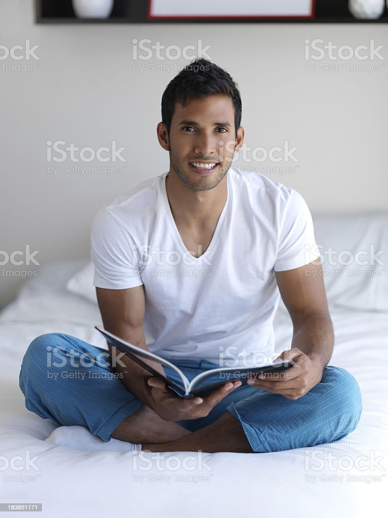 Latin man sitting in bed reading a book royalty-free stock photo