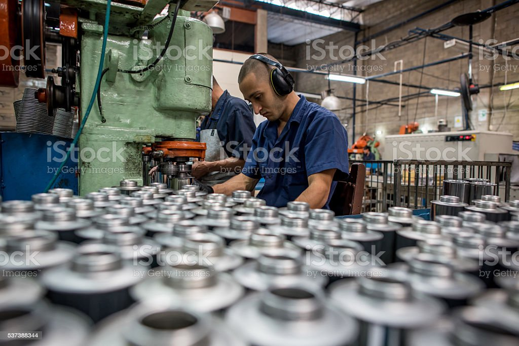 Latin man working at a metal factory stock photo