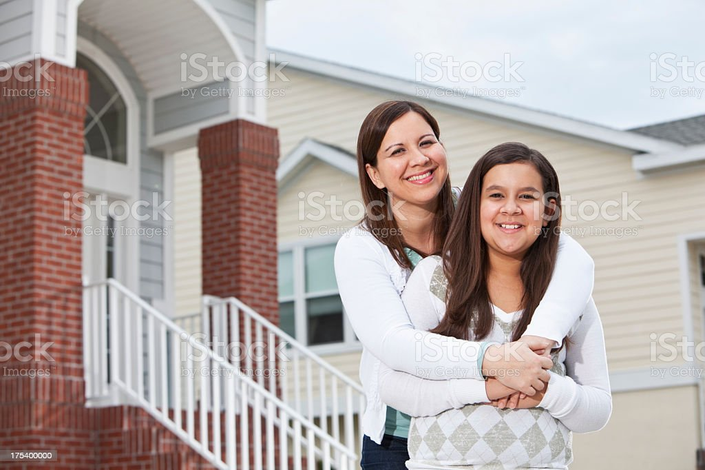 Latin mother and daughter outside townhouse stock photo