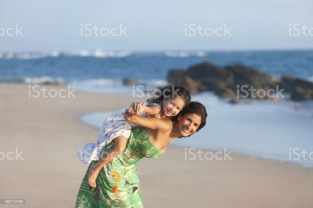 Latin mother and daughter playing at the beach royalty-free stock photo