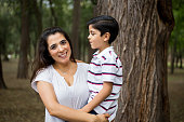 Latin mother carrying boy and smiling at camera