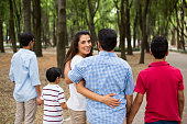 Latin mother walking with family and smiling at camera