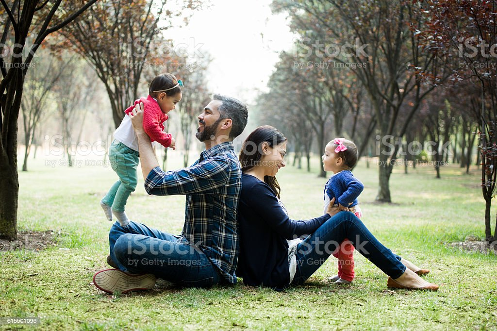 Latin parents sitting back to back and holding their daughters stock photo