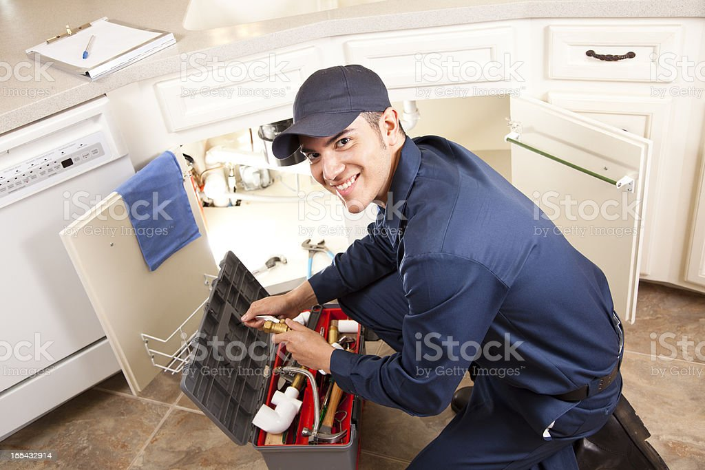 Latin Plumber, repairman working under sink, home kitchen. Service industry. stock photo
