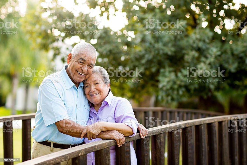 Latin senior couple posing on bridge stock photo