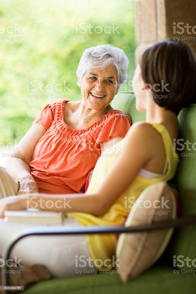 Latin senior talking with granddaughter stock photo