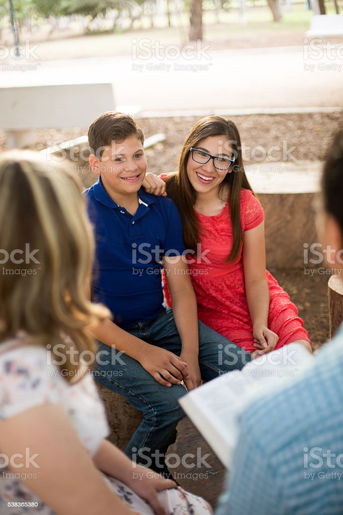 Latin siblings sitting and smiling at parents stock photo