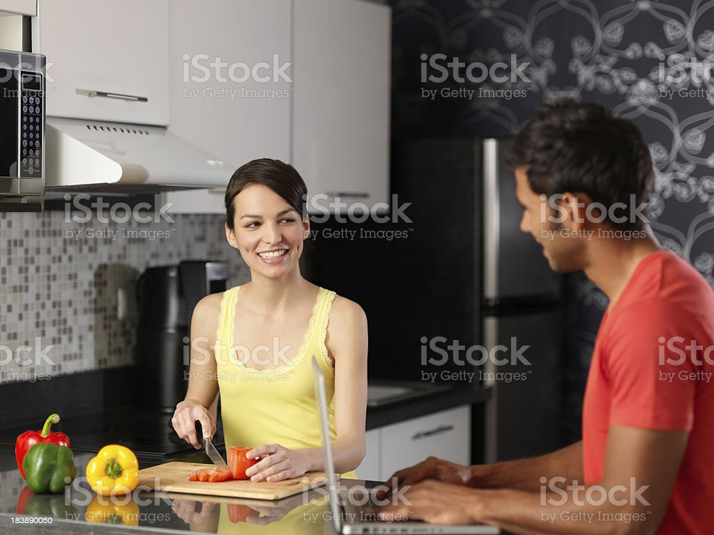 Latin woman and man hanging out in the kitchen royalty-free stock photo