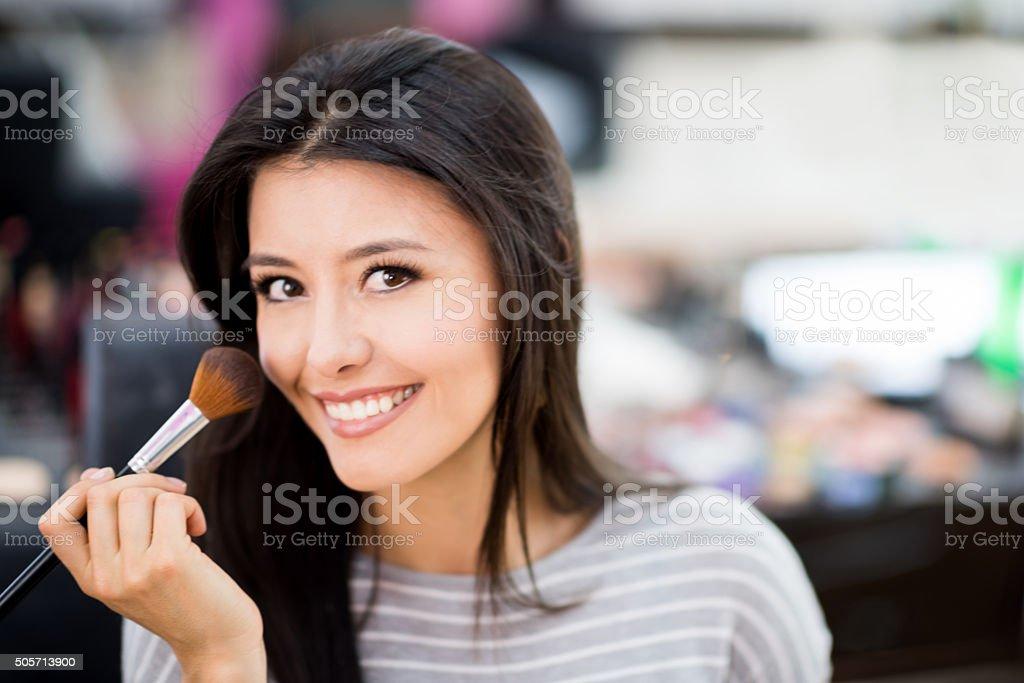 Latin woman applying makeup stock photo