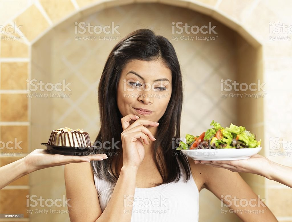 Latin woman choosing between salad and cake royalty-free stock photo