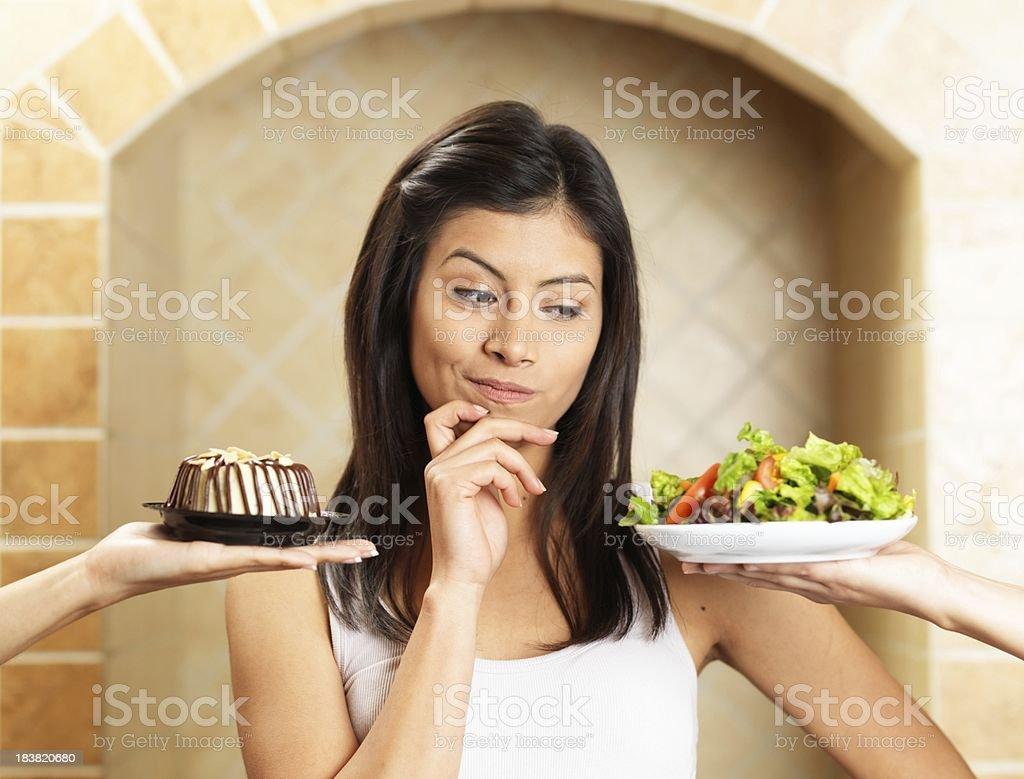 Latin woman choosing between salad and cake royalty-free stock photo