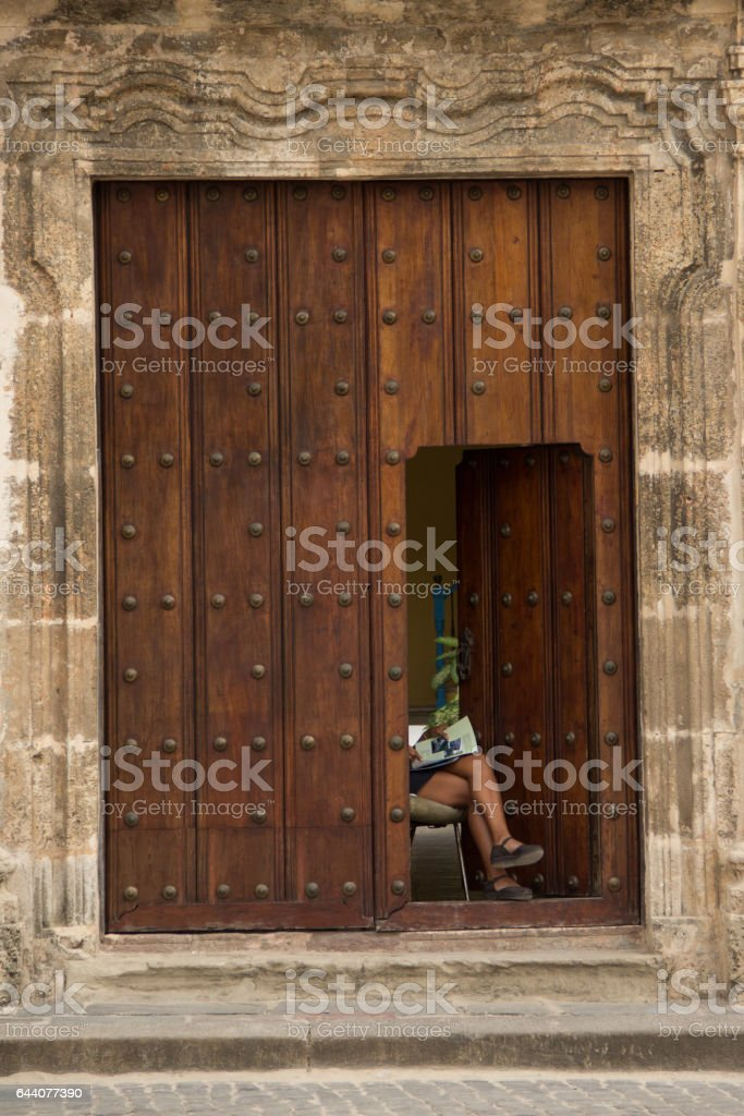 Latin woman reading on an wooded entrance of building stock photo