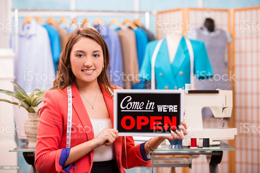 Latin woman small business owner. Fashion designer, boutique. Open sign. stock photo