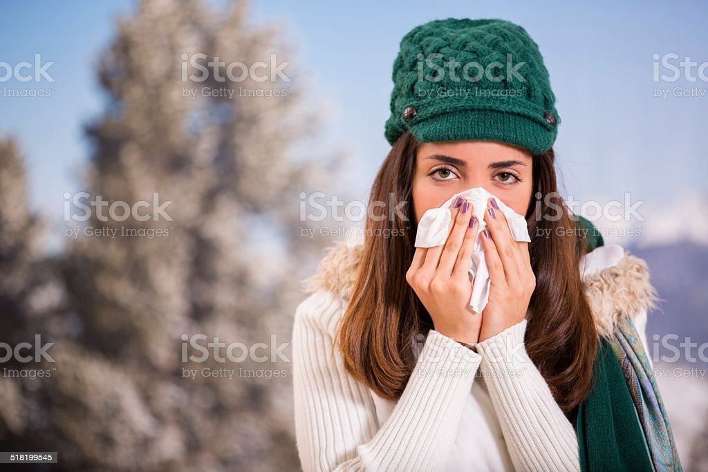 A sick, Latin descent young woman sneezes into a tissue while outside...
