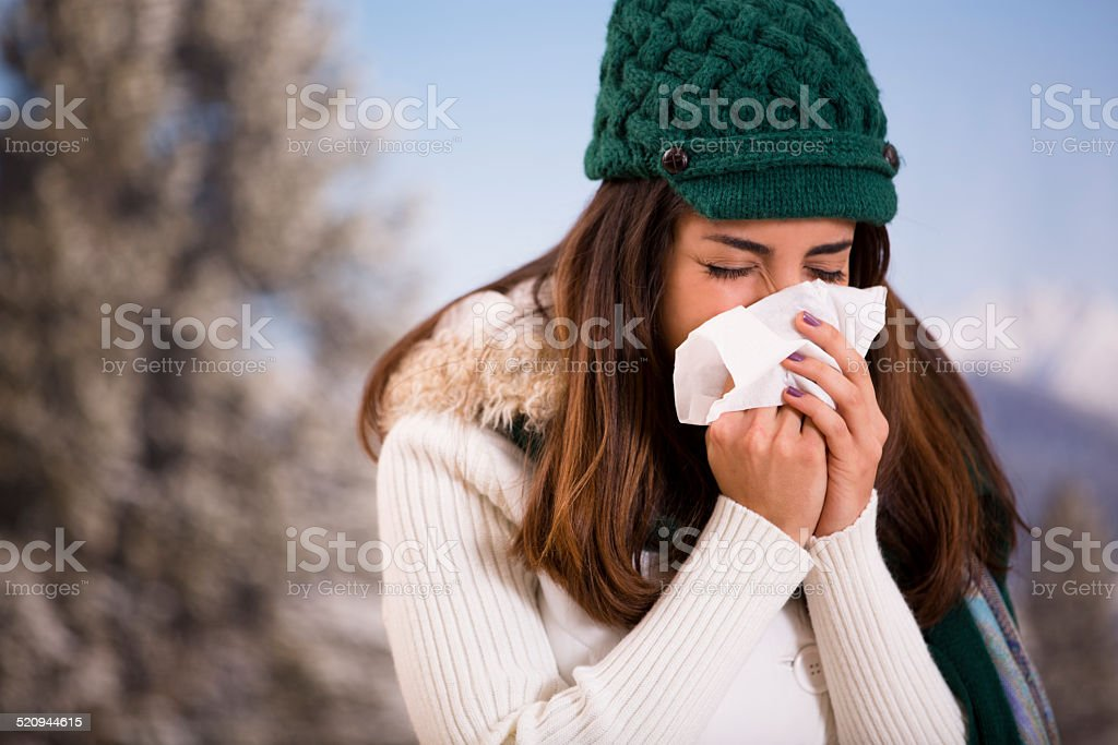 Latin woman with flu or allergies sneezes while outside. Winter. stock photo