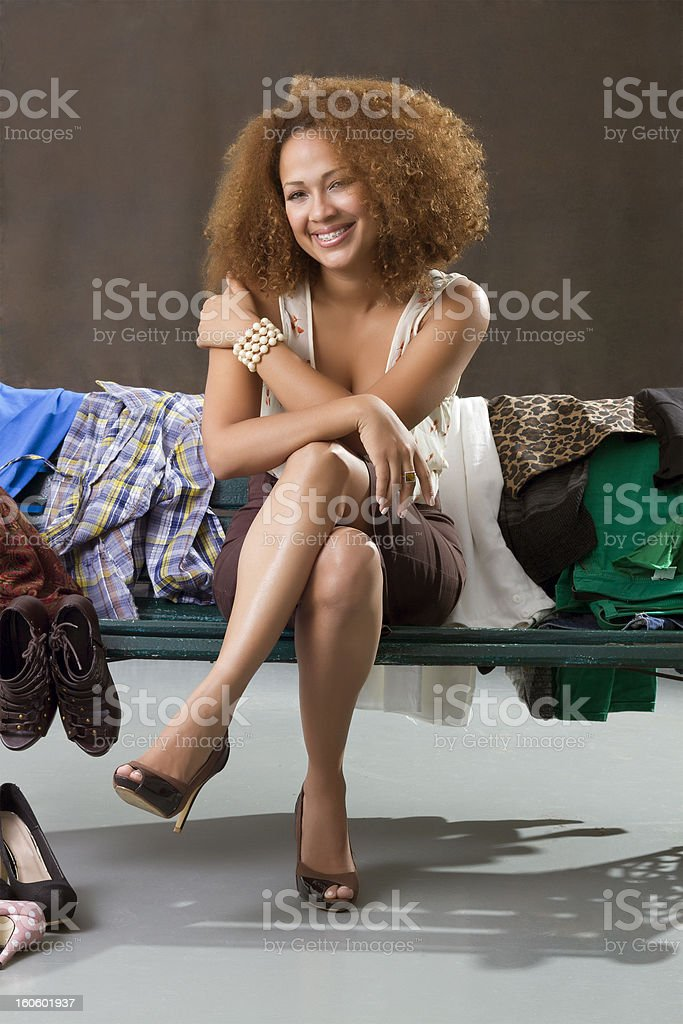 Latin woman with many clothes sitting on a bench royalty-free stock photo