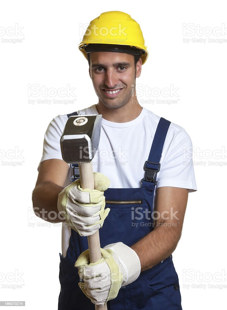 Latin worker using his sledgehammer royalty-free stock photo
