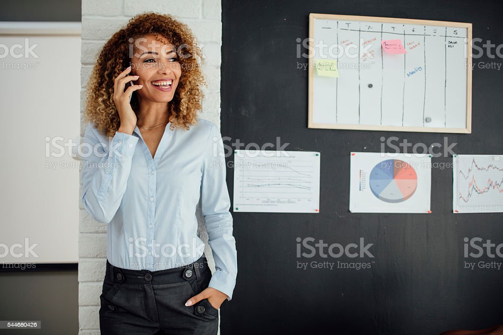 Latina Businesswoman Talking On The Phone In Her Office. stock photo